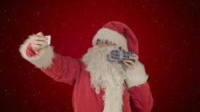 拿着一个大礼物的圣诞老人做在智能手机的一selfie在与雪的红色背景 图库摄影