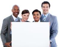 拿着一个大空白看板卡的企业小组 免版税库存图片