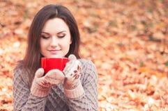 拿着一个大红色杯子和嗅到茶的少妇 免版税库存照片