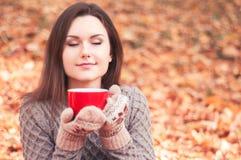 拿着一个大红色杯子和嗅到茶的少妇 免版税库存图片