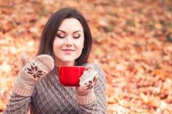 拿着一个大红色杯子和嗅到茶的少妇 库存照片