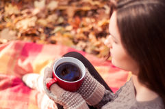 拿着一个大红色杯子用茶的少妇 免版税库存照片
