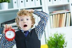 拿着一个大红色闹钟在他的手上的失望的孩子上司建议您为工作是晚 图库摄影