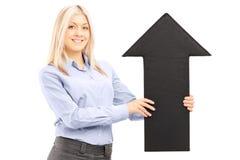 拿着一个大黑箭头的白肤金发的微笑的妇女指向  免版税库存图片