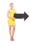 拿着一个大黑箭头的年轻白肤金发的妇女 图库摄影