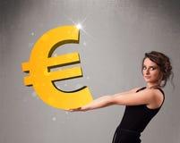 拿着一个大3d金欧元标志的美丽的女孩 免版税库存图片