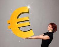 拿着一个大3d金欧元标志的美丽的女孩 免版税库存照片