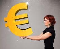 拿着一个大3d金欧元标志的美丽的女孩 图库摄影