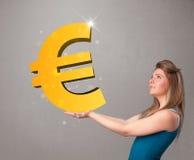 拿着一个大3d金欧元标志的美丽的女孩 免版税图库摄影