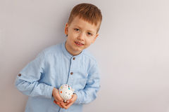 拿着一个存钱罐或钱箱的逗人喜爱的小男孩 免版税库存图片