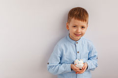 拿着一个存钱罐或钱箱的逗人喜爱的小男孩 库存照片