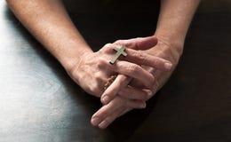 拿着一个宗教十字架的女性手祈祷为和平 图库摄影