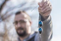 拿着一个定制的勾子和诱饵的渔夫 库存照片