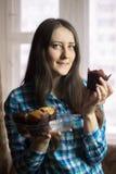 拿着一个容器被烘烤的松饼的女孩 免版税库存照片