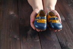 拿着一个对小的鞋子的未来父母 免版税库存图片