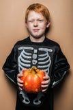 拿着一个小南瓜的年轻红色头发男孩为万圣夜 免版税库存照片