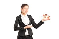 拿着一个小玩具房子的女实业家 库存图片