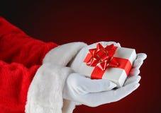 拿着一个小的圣诞节礼物的圣诞老人 库存图片