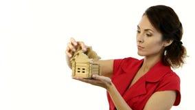 拿着一个小的房子在她的手上的恼怒的妇女和毁坏得在家 股票视频