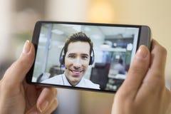 拿着一个巧妙的电话的一只女性手的特写镜头在skype vi期间 免版税库存图片