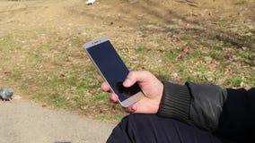 拿着一个巧妙的电话的人的手 影视素材