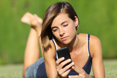 拿着一个巧妙的电话的俏丽的少年女孩说谎在草 库存图片