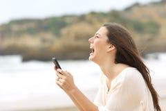 拿着一个巧妙的电话的女孩绝望地哭泣 图库摄影
