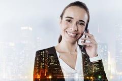 拿着一个巧妙的电话的快乐的妇女在她的耳朵附近 库存照片
