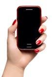 拿着一个巧妙的电话的端庄的妇女手 图库摄影