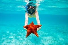 拿着一个巨型海星的少妇 库存照片