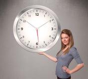 拿着一个巨大的时钟的可爱的夫人 免版税库存图片