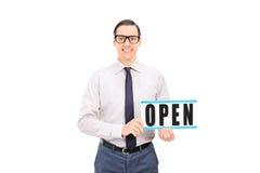 拿着一个开放标志的商店经理 免版税库存图片