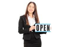 拿着一个开放标志的女性零售商 免版税库存照片