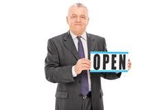 拿着一个开放标志的成熟商人 免版税库存图片