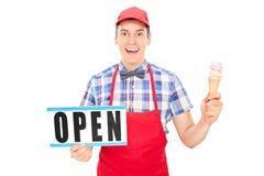 拿着一个开放标志的激动的冰淇凌供营商 库存图片