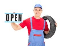 拿着一个开放标志的男性技工 库存图片