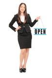 拿着一个开放标志的年轻女性零售商 库存照片