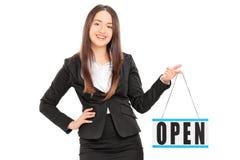 拿着一个开放标志的年轻女性零售商 免版税库存照片