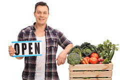 拿着一个开放标志的年轻市场供营商 免版税库存图片
