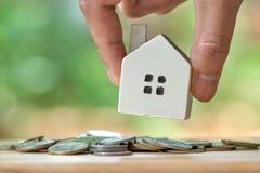 拿着一个式样房子模型的商人在堆被安置硬币 使用作为背景企业概念和房地产概念 免版税库存图片
