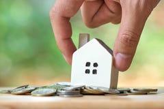 拿着一个式样房子模型的商人在堆被安置硬币 使用作为背景企业概念和房地产概念 库存照片