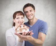 拿着一个式样房子的夫妇的综合图象 库存照片