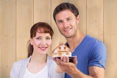 拿着一个式样房子的夫妇的综合图象 免版税库存图片