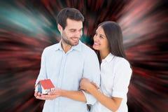 拿着一个式样房子的有吸引力的年轻夫妇的综合图象 免版税库存图片