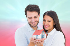 拿着一个式样房子的有吸引力的年轻夫妇的综合图象 库存图片