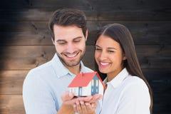 拿着一个式样房子的有吸引力的年轻夫妇的综合图象 免版税库存照片