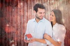拿着一个式样房子的有吸引力的年轻夫妇的综合图象 免版税图库摄影