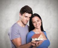 拿着一个式样房子的年轻夫妇的综合图象 免版税库存图片