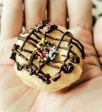 拿着一个微型多福饼的手 黑色接近的耳机图象软绵绵地查出话筒填充白色 免版税库存照片