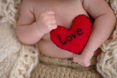 拿着一个心形的枕头的婴孩 免版税图库摄影